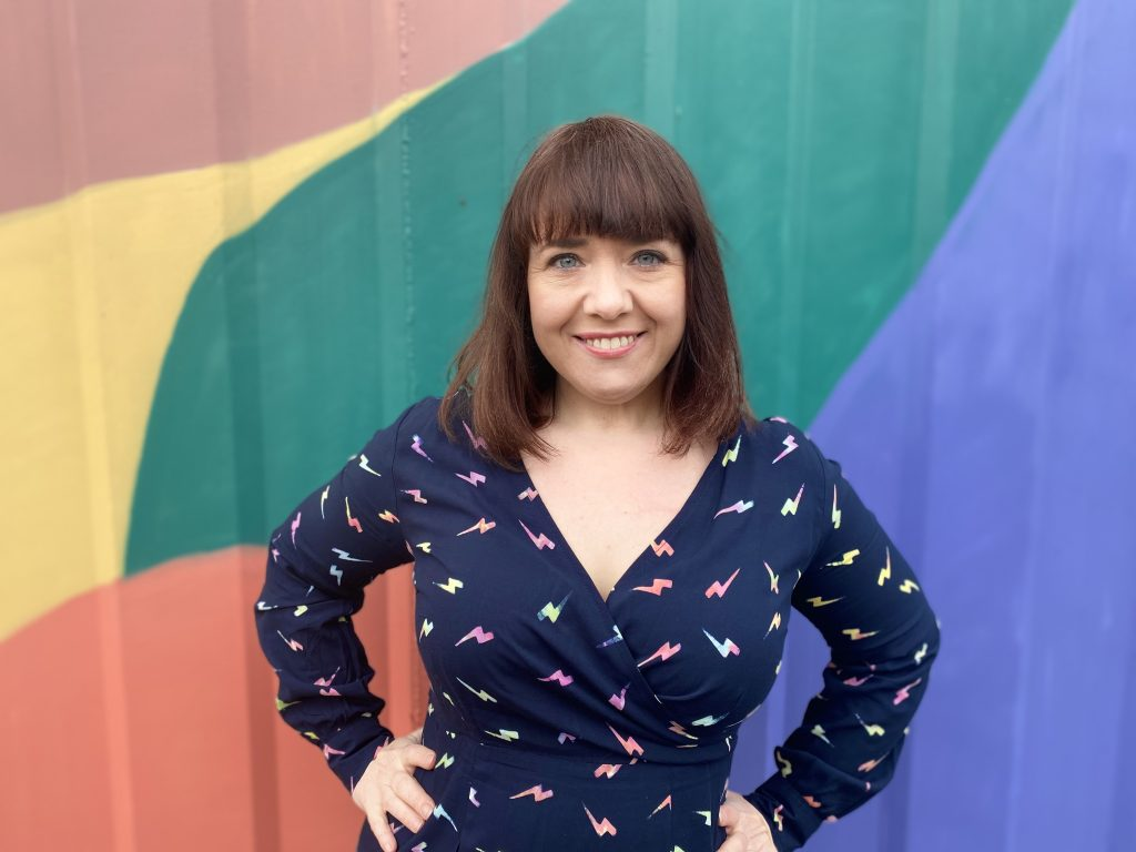 Isabel is a white woman with shoulder length brown hair with a fringe. She is standing in front of a colourful wall with her hands on her hips, smiling at the camera..